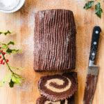 Top down view of a Christmas chocolate yule log on a wooden board, with two slices cut off
