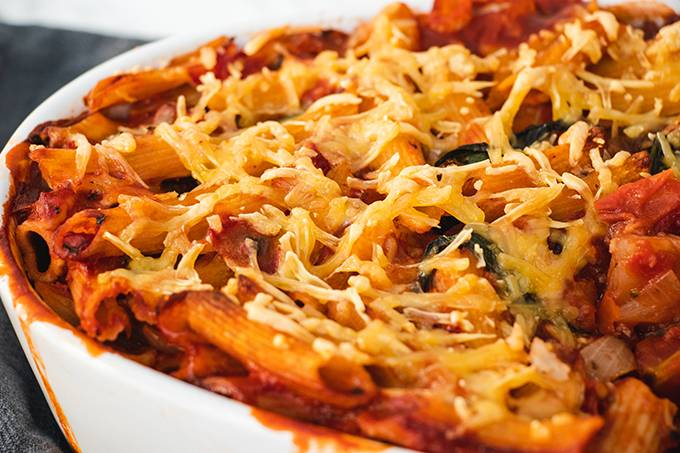 Close up of a dairy free pasta bake in a white oven dish, with crispy cheese on the top