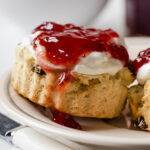 Close up of a gluten and dairy free scone topped with cream and jam.