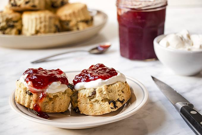 A scone on a white plate, cut in half and topped with cream and jam.