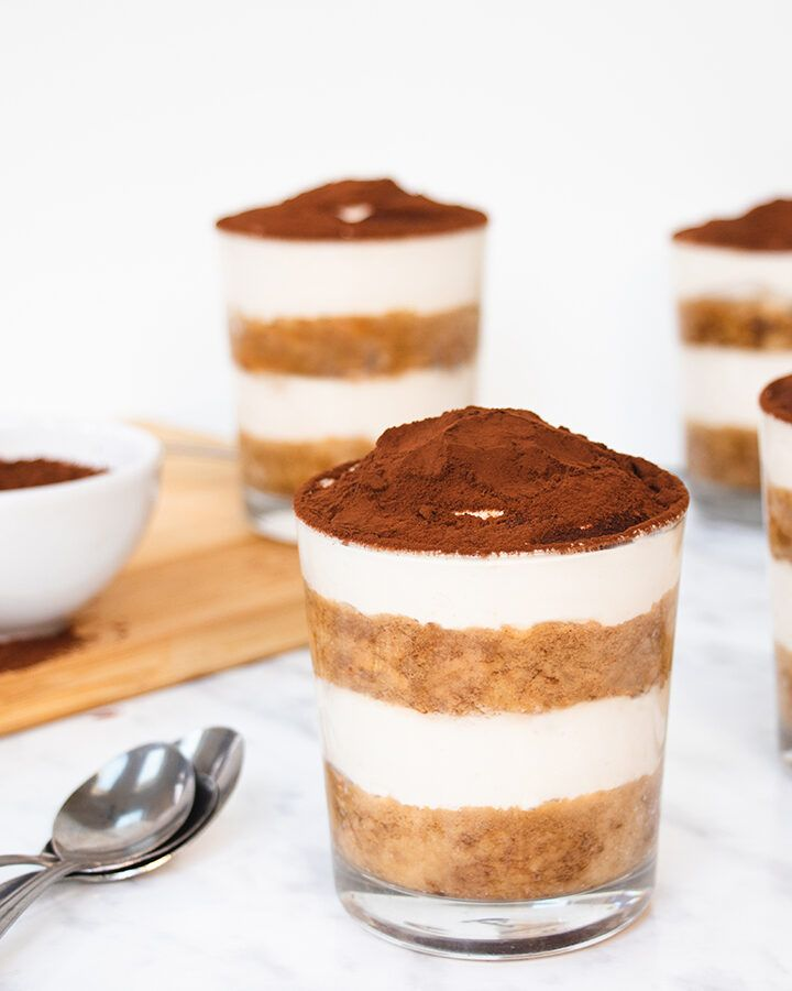Four single portion pots of layered tiramisu, each dusted with cocoa powder