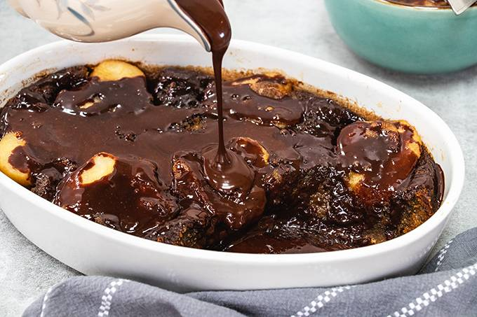 A pear and ginger pudding in a white dish, with chocolate sauce being poured on top from a jug.
