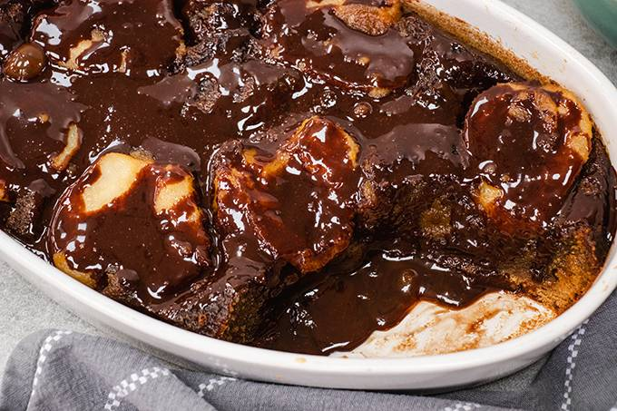 Pear and ginger pudding in a white dish, with chocolate sauce drizzled over the top.