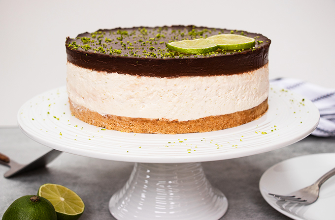 A chocolate and lime cheesecake on a white cake stand.