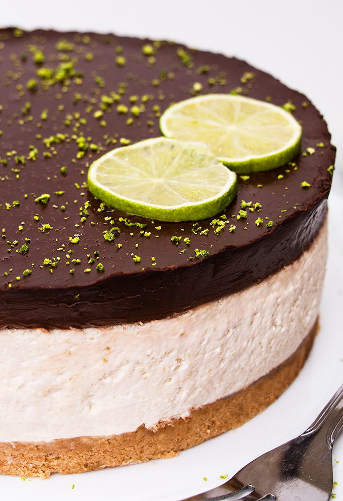 Close up of a dairy free lime cheesecake with a chocolate ganache topping and two lime slices as decoration.
