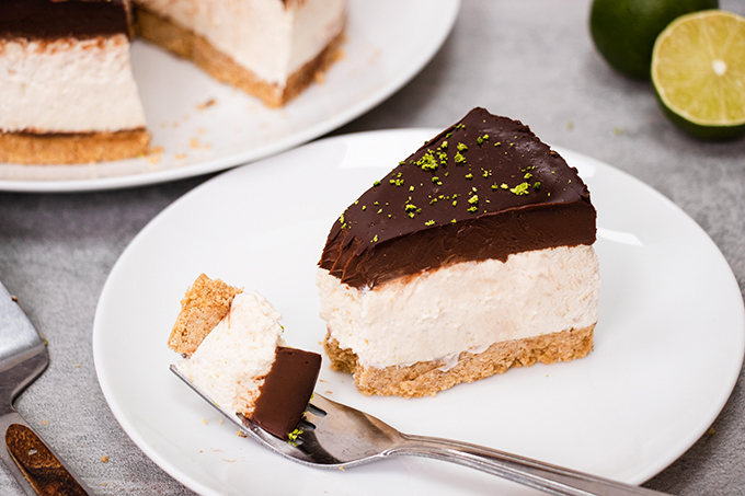 A slice of dairy free chocolate and lime cheesecake on a white plate with a forkful taken off the end.