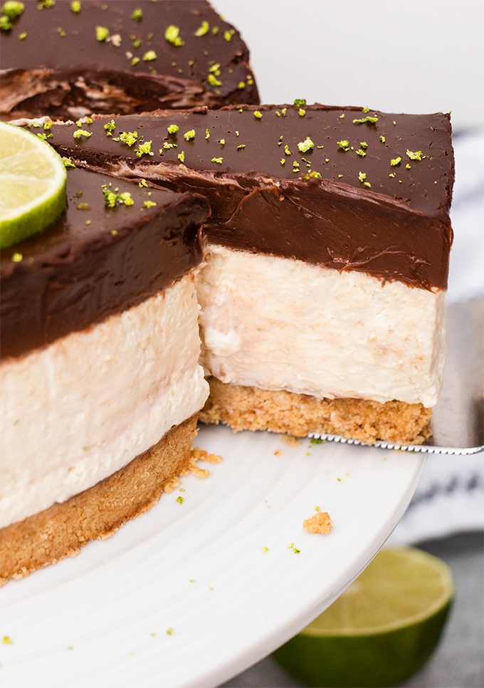 Close up of a slice being taken out of dairy free lime cheesecake with a chocolate ganache topping.