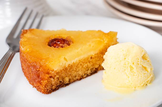 One slice of pineapple upside down cake on a white place with a scoop of vanilla ice cream next to it.