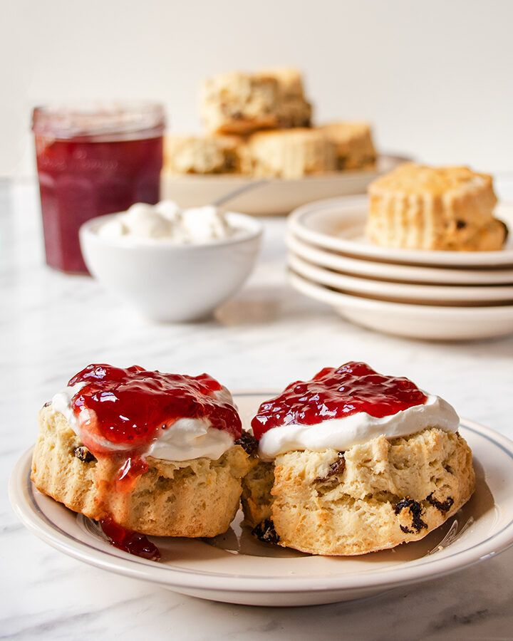 A sultana scone on a white plate, cut in half and topped with cream and jam.