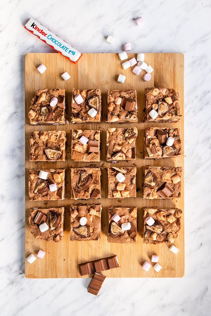 Top down view of 16 squares of Kinder rocky road on a wooden board.