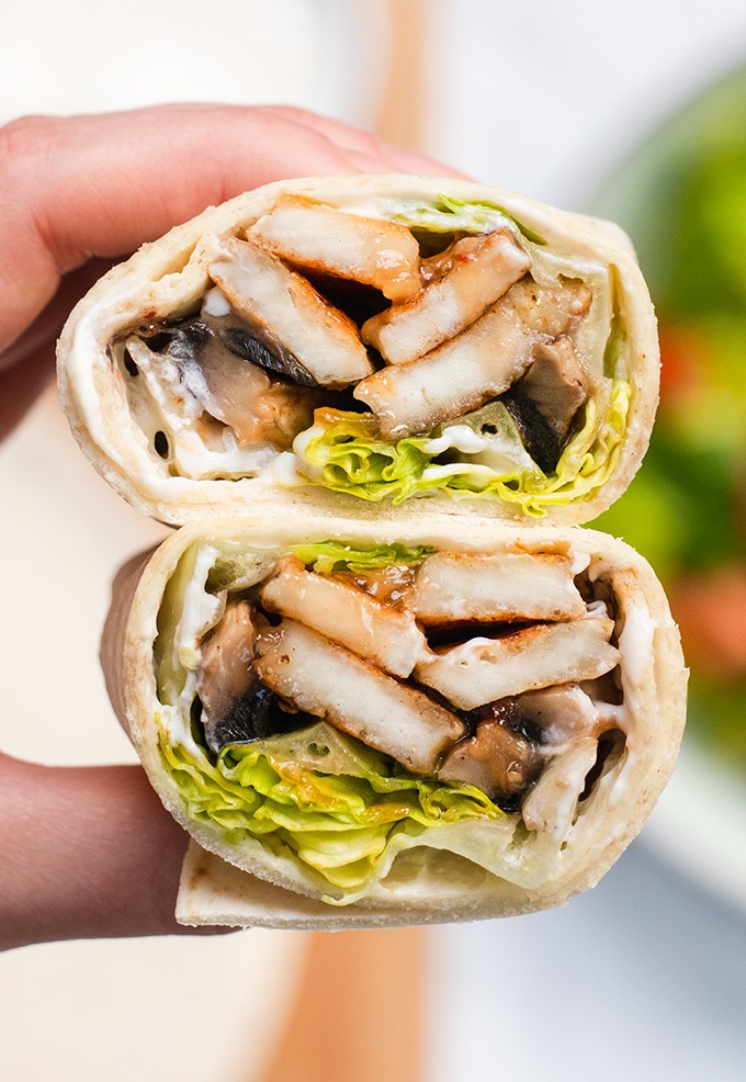 Close up of a mushroom and halloumi wrap that has been cut in half.