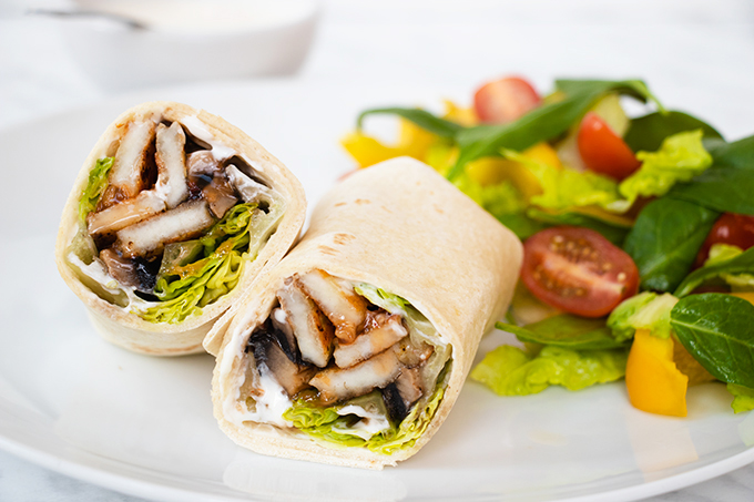 A copycat Nandos mushroom and halloumi wrap on a white plate, cut in half, with some salad next to it.