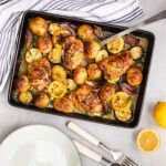 Top down view of a lemon and garlic chicken tray bake, with some of the chicken and vegetables in a bowl next to it.