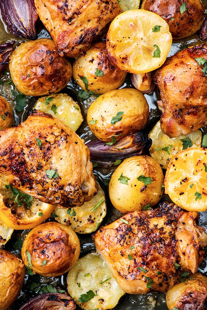 Close up of roast lemon and garlic chicken thighs, potatoes and vegetables on a baking tray.