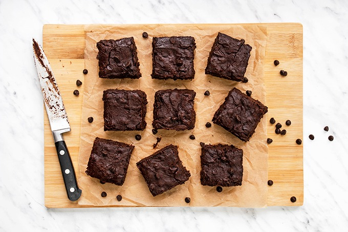 Top down view of fudgy vegan brownies on a wooden board, with a knife next to them and chocolate chips scattered around.