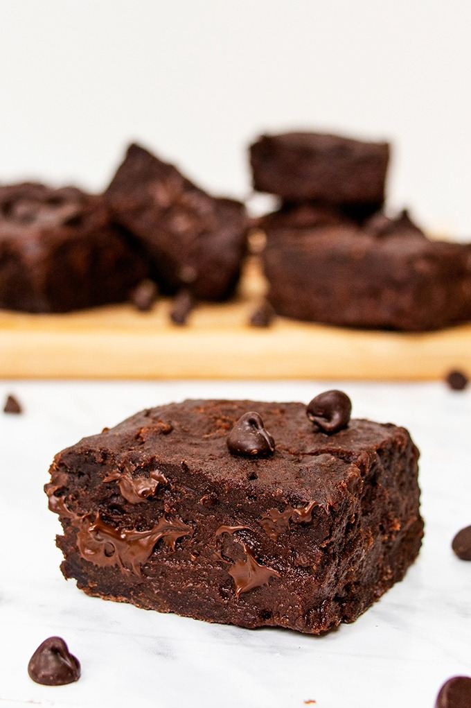 Close up of a gooey vegan date brownie, with chocolate chips scattered around and other brownies on a wooden board in the background.