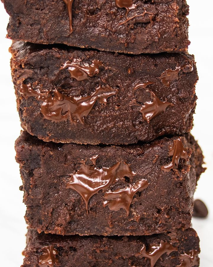 Close up of a stack of gooey vegan date brownies.