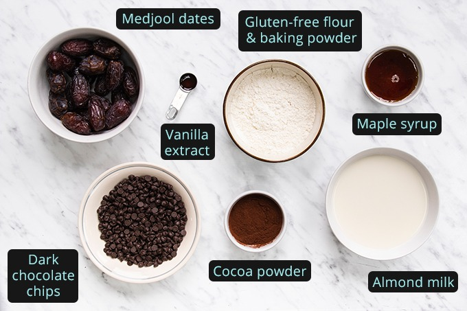 Top down view of all ingredients required to make vegan date brownies, laid out in bowls.