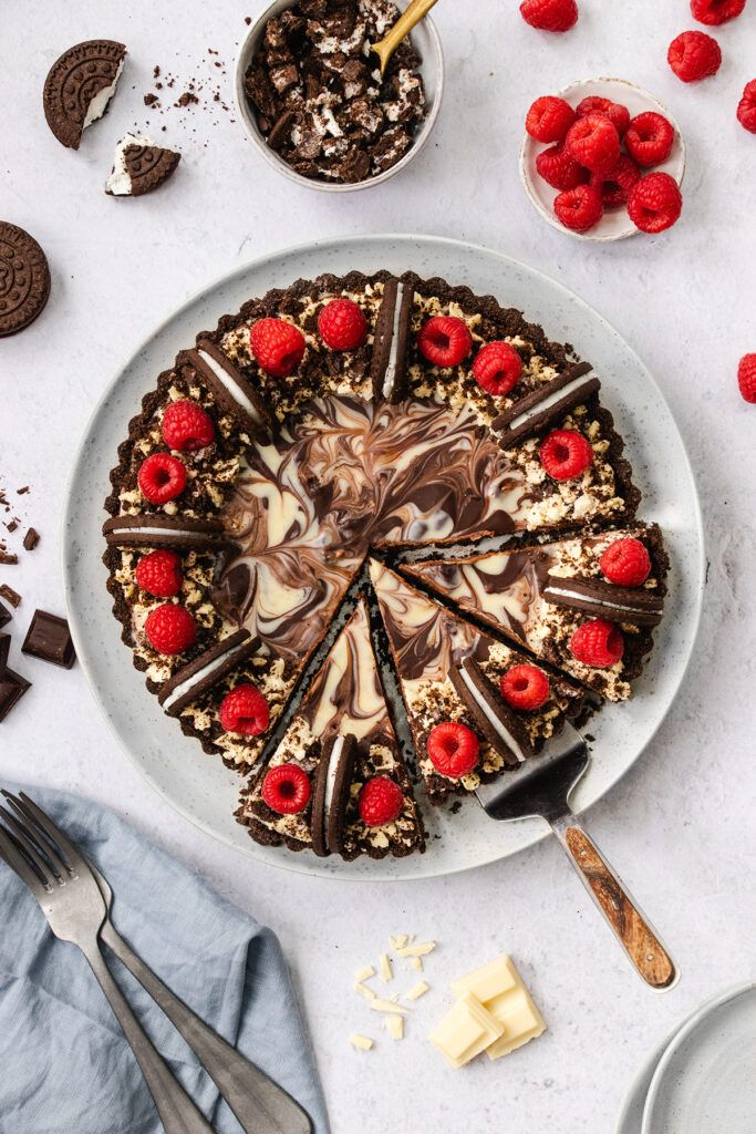 Top down view of a chocolate Oreo tart, decorated with raspberries.