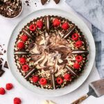 Top down view of a chocolate marble tart, decorated with raspberries and cookies and cream biscuits.