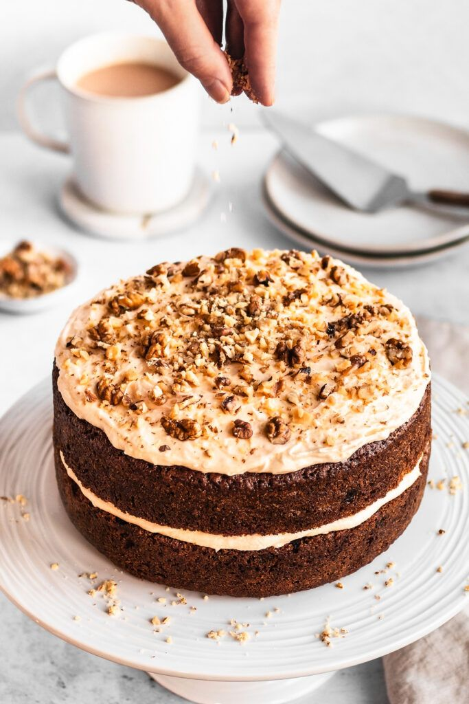 A carrot cake with frosting, being sprinkled with chopped walnuts.