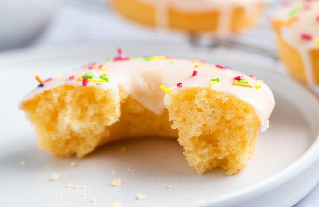 Close up of half of a no fry vanilla sprinkle doughnut.