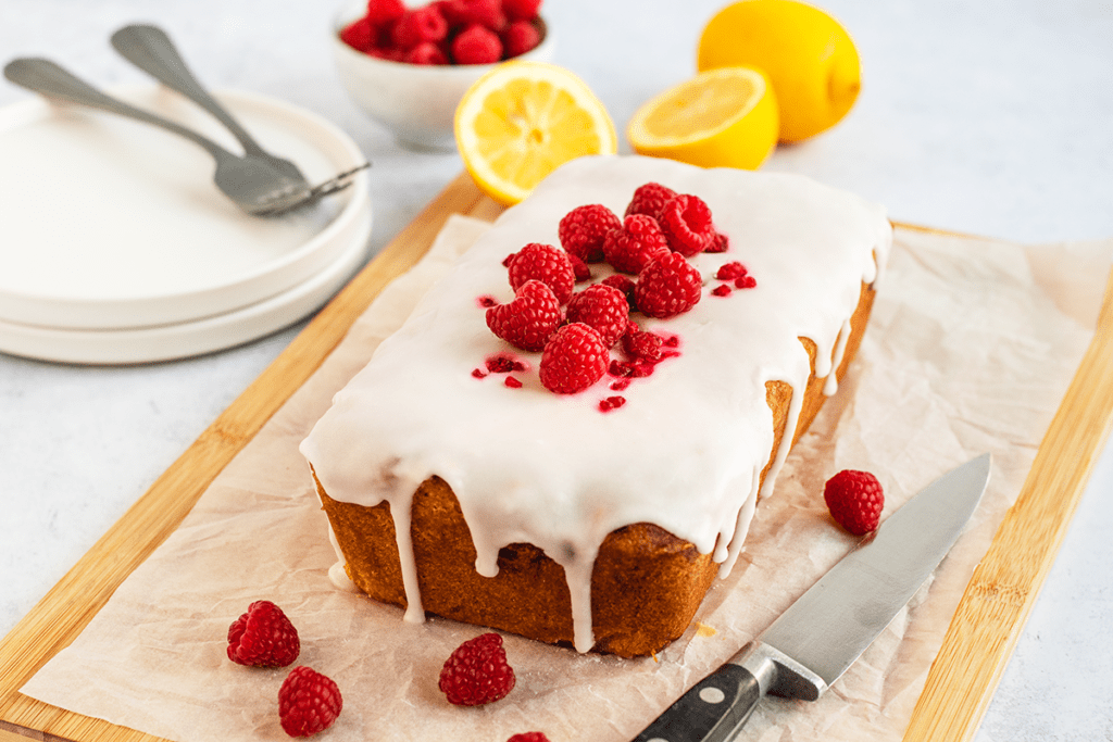 A raspberry and lemon loaf cake drizzled with an icing glaze and topped with fresh raspberries.