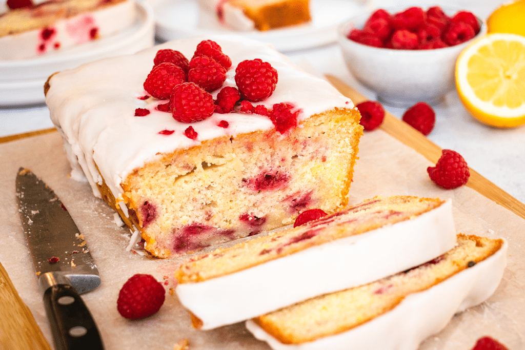 A lemon and raspberry drizzle cake, cut into slices on a board.